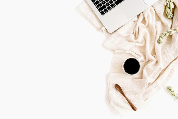 Area di lavoro con laptop, caffè, cucchiaio, fiori bianchi e tessuto beige