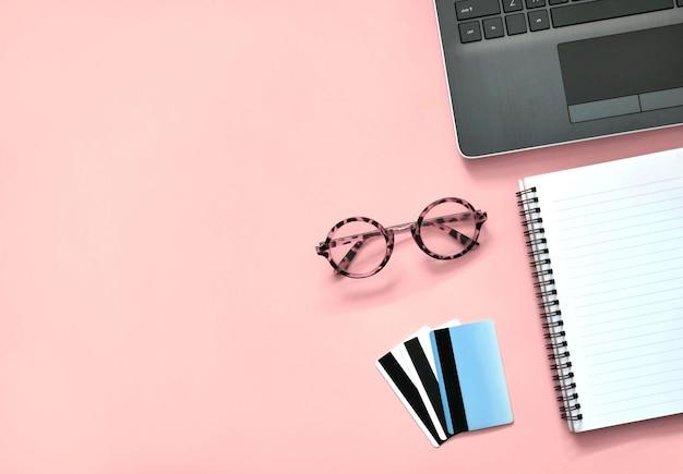 Area di lavoro con laptop, notebook, carte di credito e occhiali da vista su sfondo rosa. concetto di business dello shopping online.