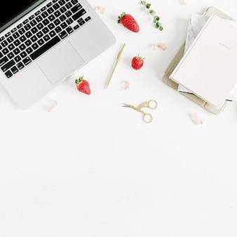 Area di lavoro con laptop, notebook, fragola, petali e rami di eucalipto su sfondo bianco. lay piatto