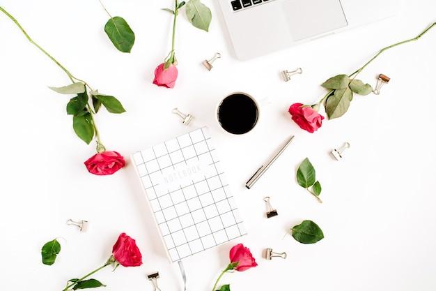 Area di lavoro con laptop, fiori di rose rosse, tazza di caffè, taccuino e clip su superficie bianca