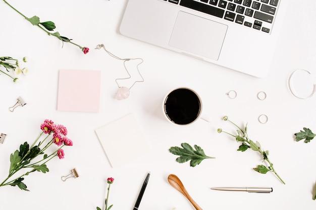 Area di lavoro con laptop, bouquet di fiori di campo, tazza di caffè, accessori femminili e roba da ufficio