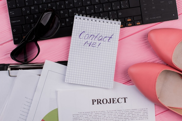 Area di lavoro con taccuino di carta scarpe occhiali su sfondo rosa