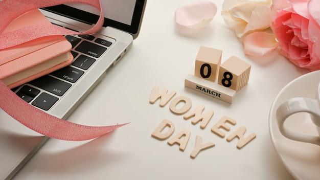 Area di lavoro nel concetto di giorno della donna con laptop, fiori, tazza di caffè e messaggio sul tavolo bianco