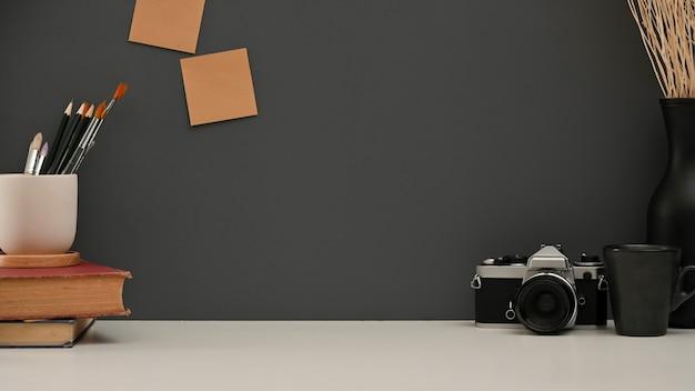 Il tavolo da lavoro con libri fornisce fotocamera e copia spazio nella stanza dell'home office