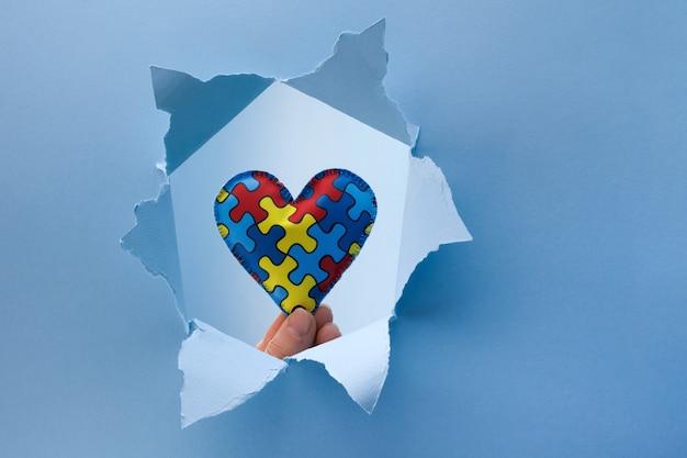 Consapevolezza mondiale dell'autismo, concetto con puzzle o motivo a puzzle sul cuore nel foro di carta tagliata