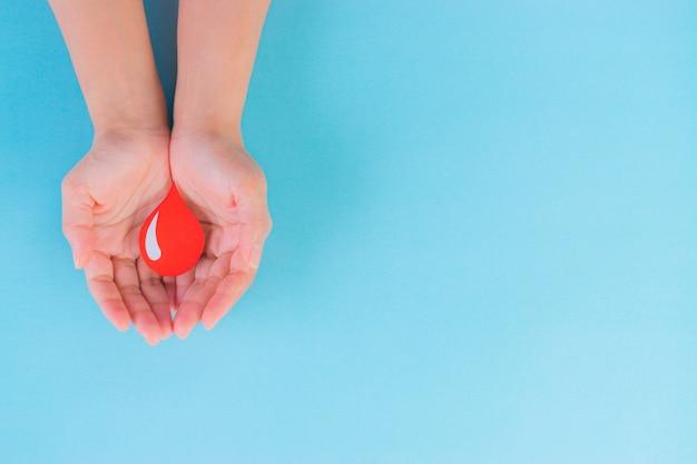 Giornata mondiale del donatore di sangue, concetto della giornata dell'emofilia. mani della donna che tengono una goccia di sangue rosso. copia spazio.