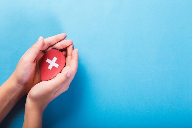 Concetto di giornata mondiale del donatore di sangue e dell'emofilia. mani della donna che tengono una goccia di sangue rosso