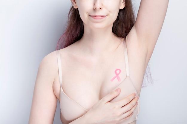 Concetto di giornata mondiale del cancro al seno. donna in reggiseno con nastro rosa dipinto sul petto. ottobre mese della consapevolezza del cancro al seno