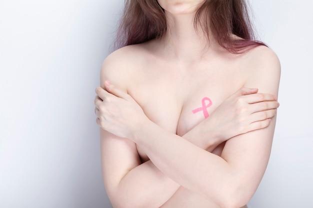 Concetto di giornata mondiale del cancro al seno. la donna si copre il petto con le mani con nastro rosa dipinto. ottobre mese della consapevolezza del cancro al seno.
