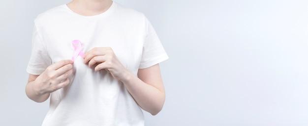Concetto di giornata mondiale del cancro al seno. la donna in maglietta bianca tiene il nastro rosa in mano