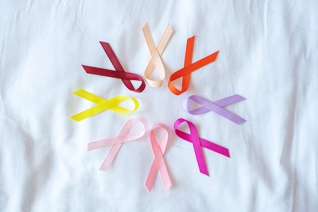 Giornata mondiale del cancro (4 febbraio). nastri colorati di consapevolezza; colore rosso, arancione, viola, rosa, pesca e giallo per sostenere le persone che vivono e le malattie. sanità e concetto medico