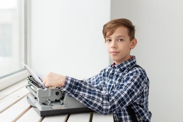 Giornata mondiale del concetto di scrittore - ragazzo con una vecchia macchina da scrivere su sfondo della finestra.