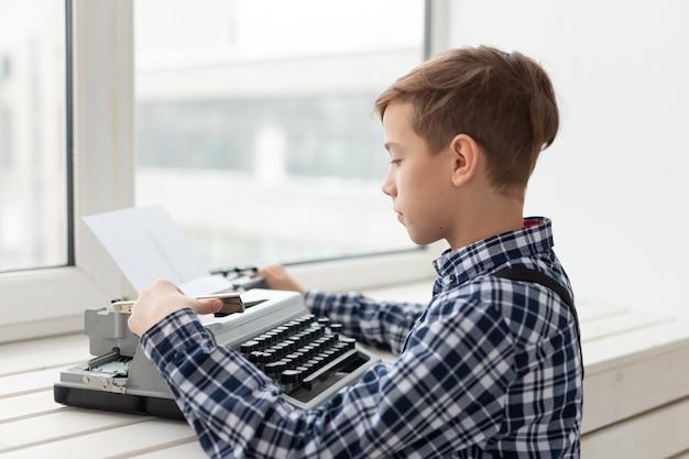 Giornata mondiale del concetto di scrittore - ragazzo con una vecchia macchina da scrivere