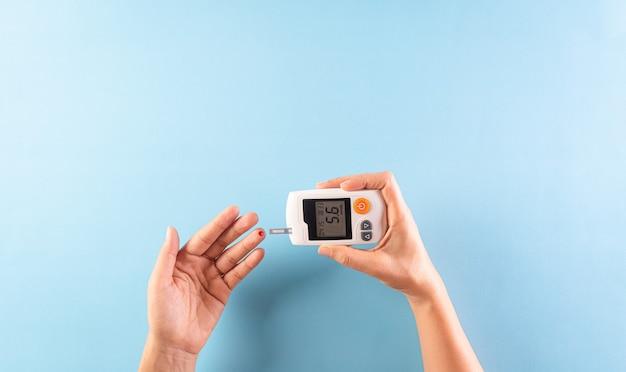 Concetto di consapevolezza della giornata mondiale del diabete. il diabetico misura il livello di glucosio nel sangue