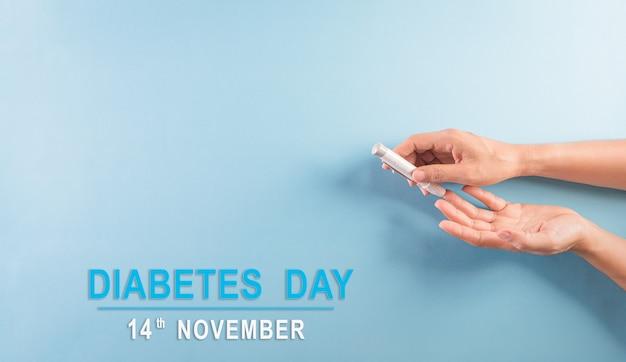 Concetto di consapevolezza della giornata mondiale del diabete il diabetico misura il livello di glucosio nel sangue