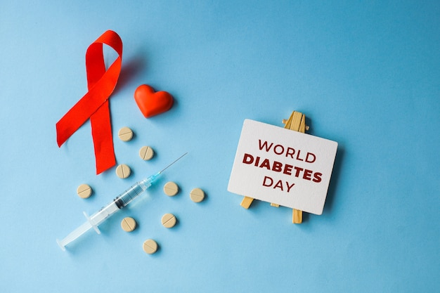 Concetto di piatto creativo per la giornata mondiale del diabete con farmaci e siringhe simbolo del sangue con nastro rosso