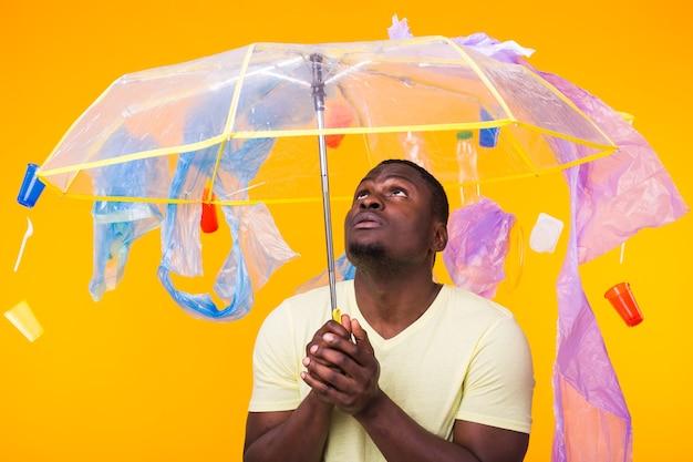 Giornata mondiale dell'ambiente, uomo di colore con in mano un ombrello pieno di plastica
