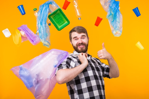Giornata mondiale dell'ambiente, problema del riciclaggio della plastica e concetto di disastro ambientale - uomo divertente che tiene il sacco della spazzatura per il riciclaggio e che mostra il pollice in su.