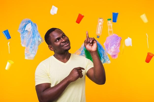 Giornata mondiale dell'ambiente, problema del riciclaggio della plastica e concetto di disastro ambientale - uomo afroamericano sorpreso che guarda nel cestino.