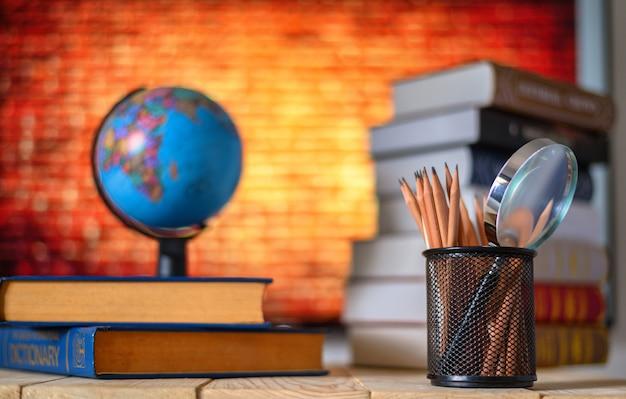 Mappamondo, lente d'ingrandimento, libri e matite