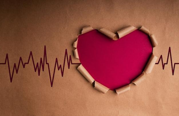 Giornata mondiale della salute. concetto internazionale della giornata mondiale del cuore. carta artigianale a forma di cuore con battito e stetoscopio all'interno. vita, amore e cura. vista dall'alto