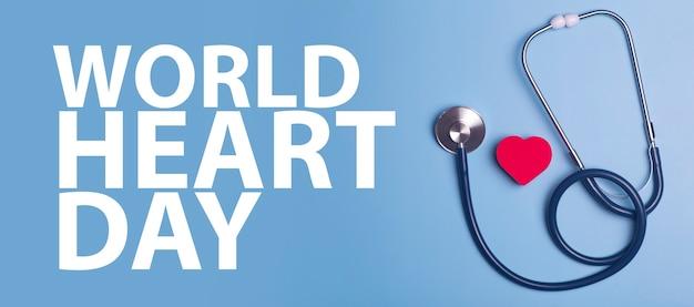 Fondo della bandiera di giornata mondiale del cuore. cuore come simbolo di salute, cura, carità, donazione e cardiologia su sfondo blu con uno statoscopio medico.
