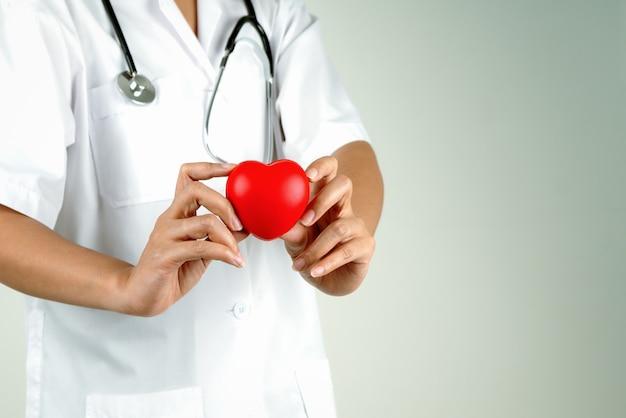 Concetto di giornata mondiale del cuore della mano del medico della donna che tiene cuore rosso