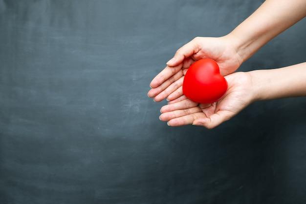 Concetto di giornata mondiale del cuore della mano della giovane donna che tiene cuore rosso