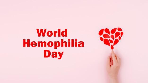 Giornata mondiale dell'emofilia sfondo poster di consapevolezza dell'emofilia gocce rosse cuore e mondo del testo
