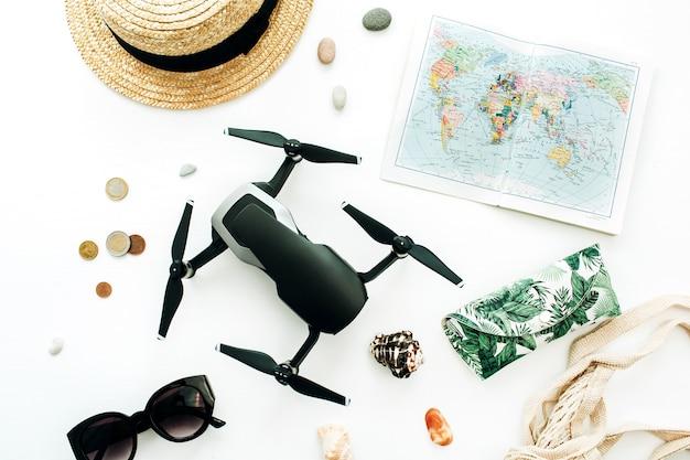 Mappa del mondo, drone, paglia, occhiali da sole, monete su sfondo bianco. disposizione piatta, vista dall'alto
