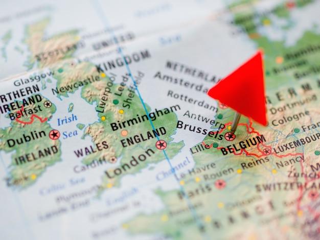 Mappa del mondo con focus sul regno del belgio. perno rosso del triangolo sulla capitale bruxelles.