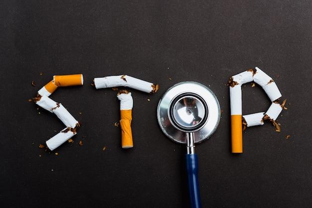 Giornata mondiale senza tabacco non fumatori close up parola stop scritto il testo della pila di sigarette o tabacco