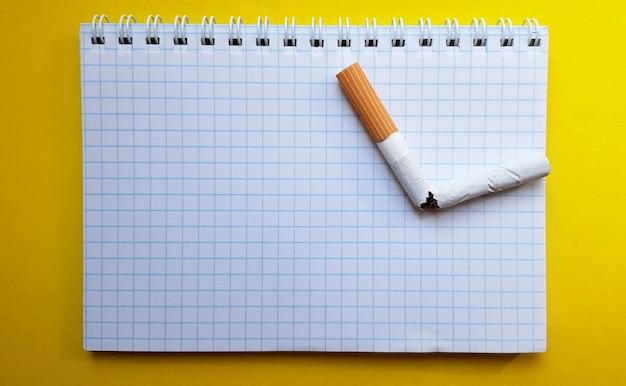 Giornata mondiale senza tabacco, giornata senza fumo. sigaretta rotta su un taccuino aziendale, posto per il testo. Foto Premium