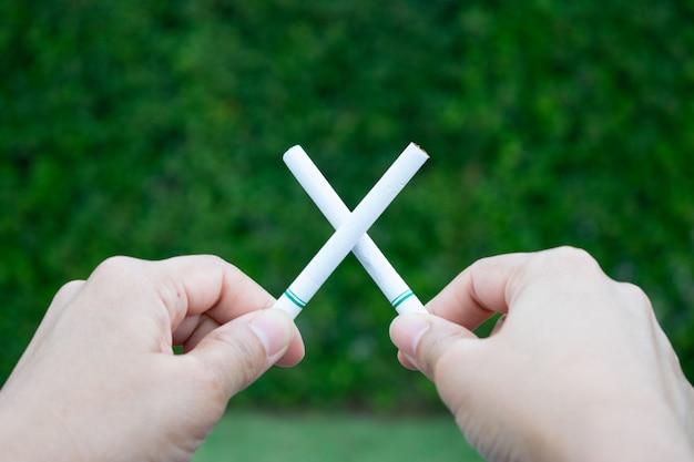 Giornata mondiale senza tabacco. smettere di fumare. chiuda sulle sigarette attraversate tenuta della mano della donna.