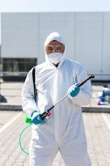 Pandemia mondiale. disinfezione in tuta e maschera protettiva, con sostanze chimiche per la disinfezione all'aperto