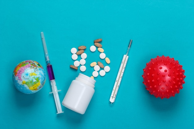 Pandemia mondiale. siringa, forniture mediche, ceppo virale, globo sul blu