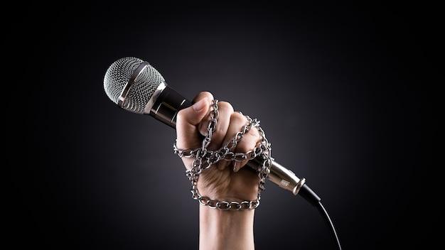 Giornata mondiale della libertà di stampa concetto mano che tiene un microfono con catena Foto Premium