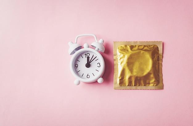 Giornata mondiale della salute sessuale o dell'aids, preservativo nella confezione e controllo delle nascite con sveglia