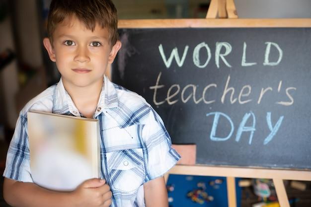Saluto della giornata mondiale dell'insegnante, allievo vicino alla lavagna, testo dell'iscrizione in gesso