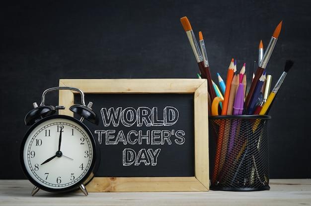 Testo del giorno dell'insegnante mondiale. lavagna con cornice in legno, scuola stazionaria e sveglia