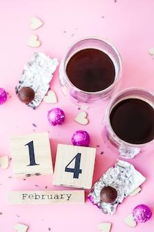 San valentino mondiale. calendario in legno con data 14 febbraio su sfondo rosa con caffè e dolci