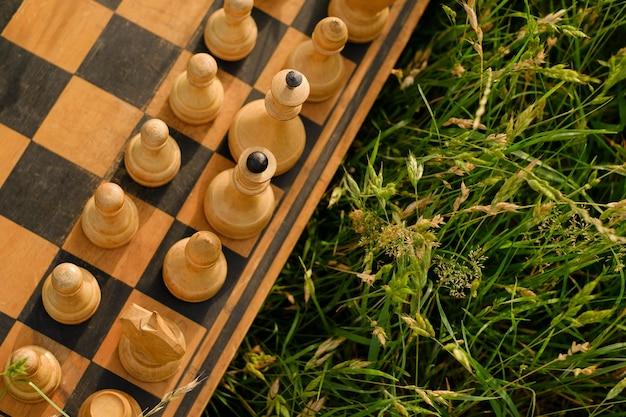 Una vecchia scacchiera consumata con pezzi di legno bianco