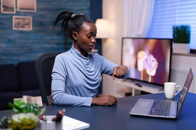 Imprenditore africano preoccupato che guarda un orologio da polso che lavora duramente per completare un grande progetto di lavoro. manager nero nervoso che fa gli straordinari lavorando sul computer.