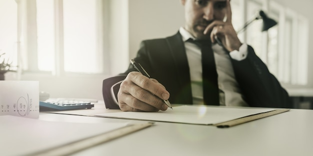 Uomo d'affari preoccupato seduto alla sua scrivania che lavora su documenti fiscali e finanziari con calcolatrice e ricevute sulla sua scrivania.