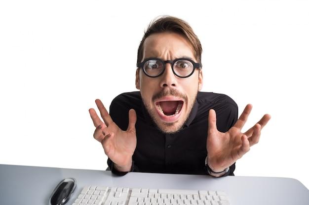 Uomo d'affari preoccupato con gli occhiali che per mezzo del computer