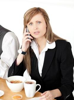 Donna di affari preoccupata che parla sul telefono mentre mangiando prima colazione