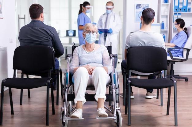 Donna anziana disabile preoccupata seduta in sedia a rotelle nell'area di attesa dell'ospedale per l'esame medico