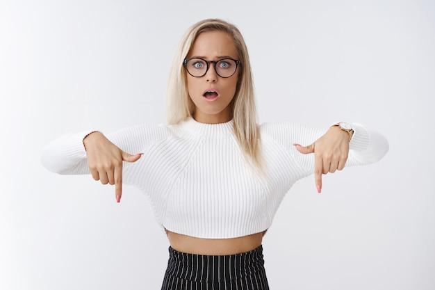 Preoccupato e insicuro giovane donna in preda al panico in piedi confuso e interrogato bocca aperta schioccando gli occhi alla telecamera incerto rivolto verso il basso facendo una domanda travagliata e incerta sul muro bianco.