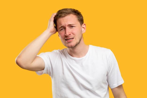 Ritratto di uomo preoccupato. ricordi tristi. ragazzo confuso che tocca la testa isolata sulla parete arancione.
