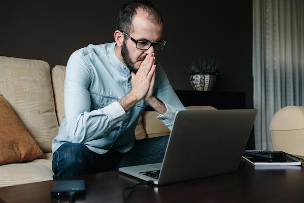 Uomo preoccupato che legge cattive notizie sul computer portatile mentre lavorando a distanza a casa. concetto di telelavoro, telelavoro e telelavoro.